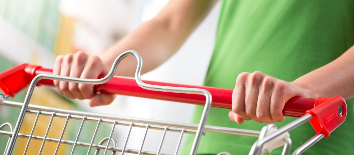 Woman in green t-shirt pushing a shopping cart at store with shelves on background.