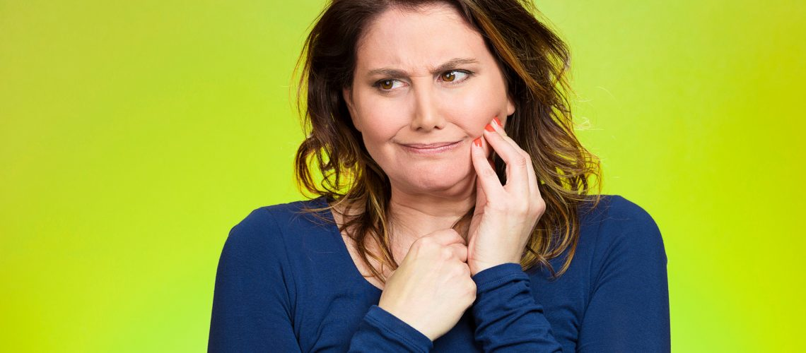 Portrait middle aged woman with sensitive tooth ache, crown problem crying from pain, touching outside mouth with hand isolated green background. Negative emotion, facial expression feeling, health